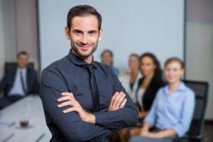 mężczyzna-uśmiecha-się-garnitur-posiedzenia-przy-stole-z-kolegami-z-tyłu_1262-826