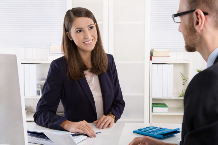 33089029 - customer and smiling female financial agent in a discussion at desk.